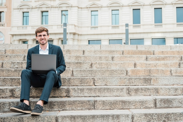 Sorrindo, retrato, de, um, jovem, homem negócios, sentar escada, usando, tablete digital Foto gratuita