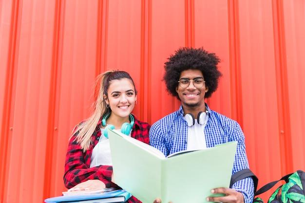 Sorrindo, retrato, de, um, jovem, macho fêmea, estudantes, estudar, junto Foto gratuita