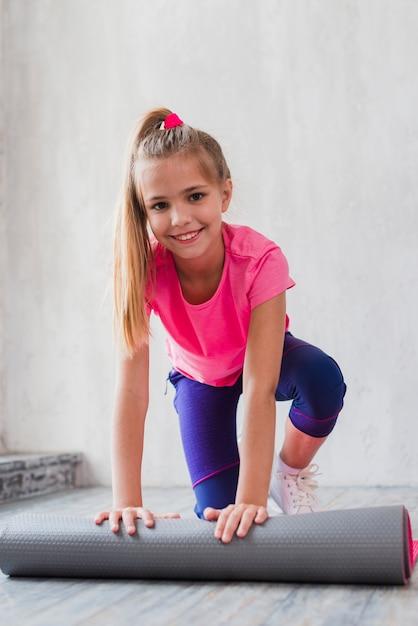 Sorrindo, retrato, de, um, loiro, menina, rolando, a, esteira exercício, frente, parede Foto gratuita