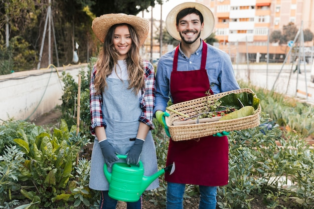 Sorrindo, retrato, de, um, macho fêmea, jardineiro, segurando, lata molhando, e, cesta, em, a, jardim Foto gratuita