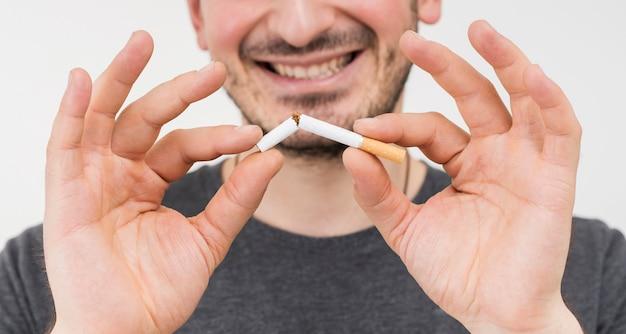 Sorrindo, retrato, de, um, mão masculina, quebrar, cigarro Foto gratuita