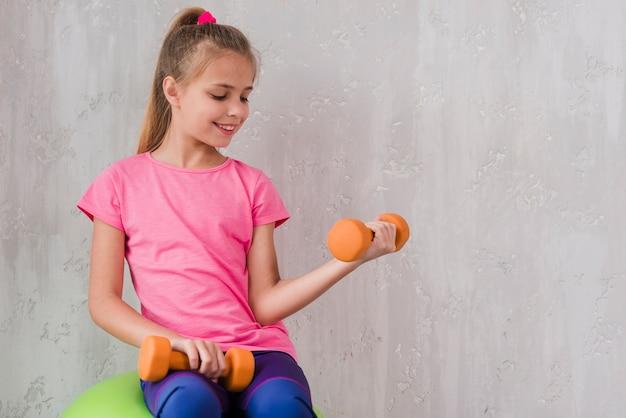 Sorrindo, retrato, de, um, menina, exercitar, com, dumbbell, contra, parede Foto gratuita