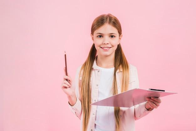 Sorrindo, retrato, de, um, menina, segurando, lápis, e, área de transferência, em, mãos, contra, rosa, fundo Foto gratuita