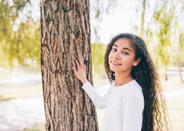 Sorrindo, retrato, de, um, menina, tocar, tronco árvore Foto gratuita