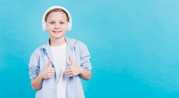 Sorrindo, retrato, de, um, menino, com, branca, headphone, ligado, seu, cabeça, mostrando, polegar cima, sinal, contra, azul, fundo Foto gratuita