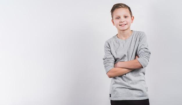 Sorrindo, retrato, de, um, menino, com, seu, braços cruzaram, olhando câmera, contra, fundo branco Foto gratuita