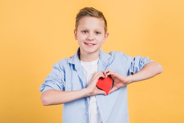 Sorrindo, retrato, de, um, menino, mostrando, forma coração vermelho, ficar, contra, amarela, fundo Foto gratuita