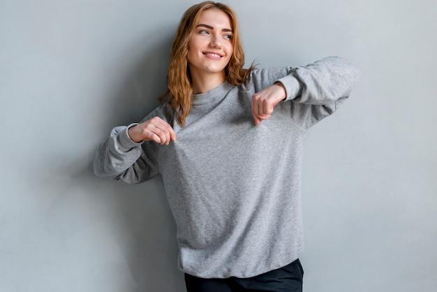 Sorrindo, retrato, de, um, mulher jovem, beliscando, dela, t-shirt, olhando, contra, cinzento, fundo Foto gratuita