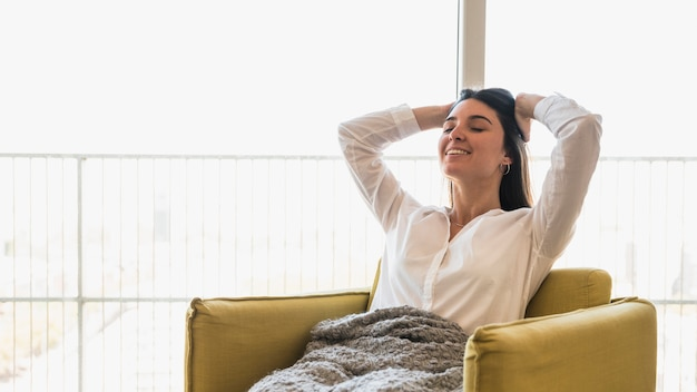 Sorrindo, retrato, de, um, mulher jovem, com, dela, mãos cabeça, sentando, ligado, poltrona Foto gratuita