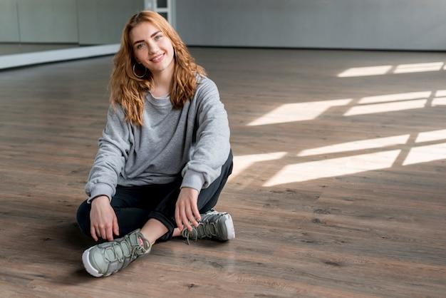 Sorrindo, retrato, de, um, mulher jovem, relaxante, ligado, assoalho hardwood, em, a, dança, estúdio Foto gratuita