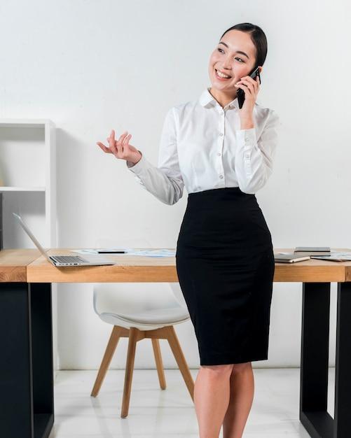Sorrindo, retrato, de, um, mulher negócios fica, frente, escrivaninha, conversa telefone móvel, gesticule Foto gratuita