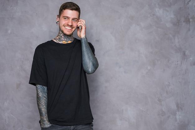 Sorrindo, retrato, de, um, tatuado, homem jovem, com, perfurado, orelhas, falando telefone móvel Foto gratuita