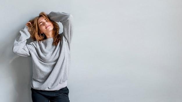 Sorrindo, retrato, jovem, mulher, contra, cinzento, parede Foto gratuita