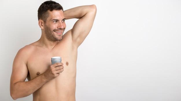 Sorrindo sem camisa charmoso homem segurando o rolo no desodorante permanente contra o pano de fundo branco Foto gratuita