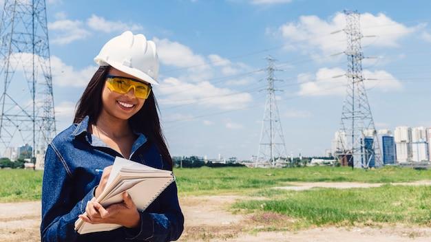 Sorrindo, senhora americana africana, em, capacete segurança, notas levando, perto, linha alta voltagem Foto gratuita