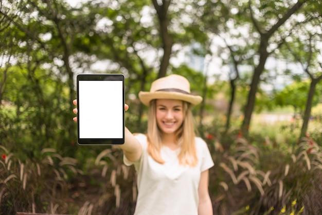 Sorrindo, senhora, em, chapéu, mostrando, tabuleta, parque Foto gratuita
