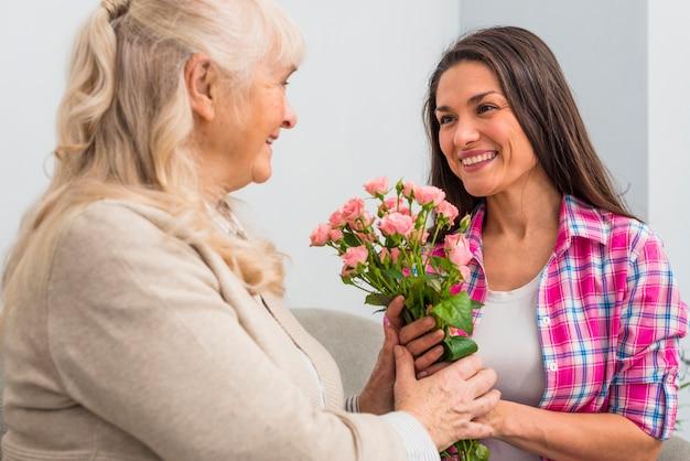 Sorrindo, sênior, mãe, e, dela, filha, segurando, rosa, buquet Foto gratuita