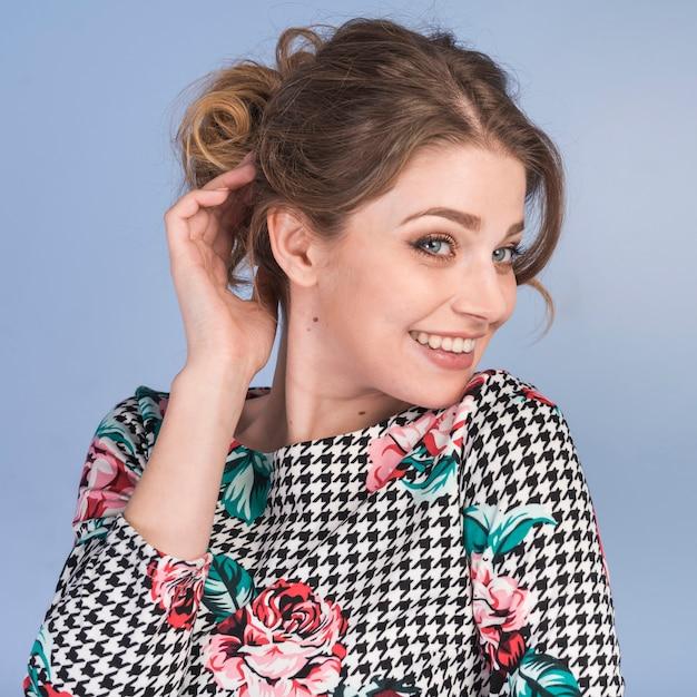 Sorrindo, tímido, mulher, em, vestido, segurando cabelo Foto gratuita