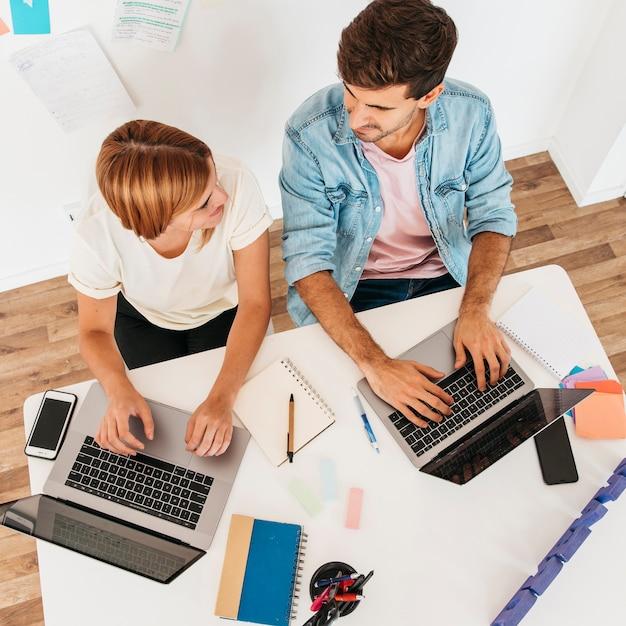 Sorrindo, trabalhando, macho fêmea, sentando, em, local trabalho, e, usando, laptops, olhando um ao outro Foto gratuita