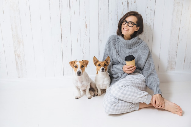Sorrir alegre jovem fêmea usa camisola de lã quente, óculos quadrados, bebe bebida quente Foto Premium