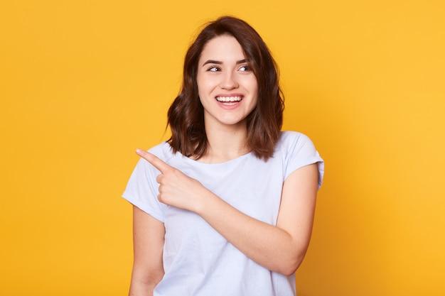 Sorrir mulher jovem e bonita veste camiseta branca casual, pontos com o dedo indicador de lado Foto gratuita