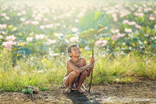 Sorriso asiático e felicidade da criança que jogam a água sob a folha dos lótus após chover o dia no campo em tailândia. Foto Premium