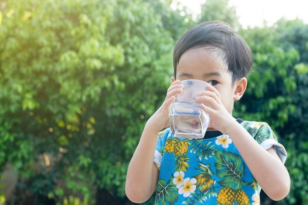 Sorriso bonito asiático menino água potável para saudável e refrescante com fundo verde árvore Foto Premium