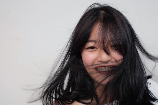 Sorriso de menina asiática com ferramenta de retenção Foto Premium