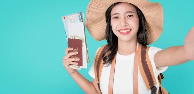 Sorriso felizmente viajante asiático da mulher que guarda o passaporte com bilhete e mapa, dinheiro. Foto Premium