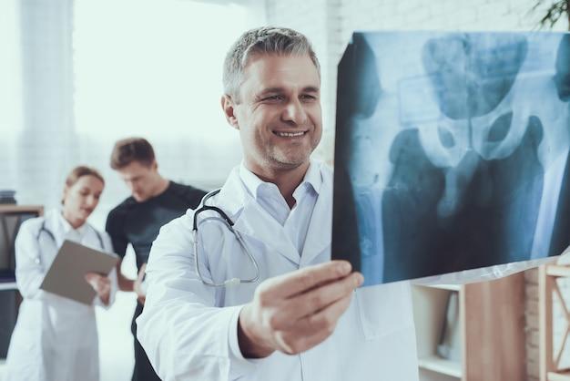 Sorriso médico está olhando para raio-x para atleta Foto Premium