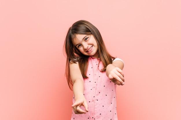 Sorrisos alegres da menina bonito que apontam para frontear. Foto Premium