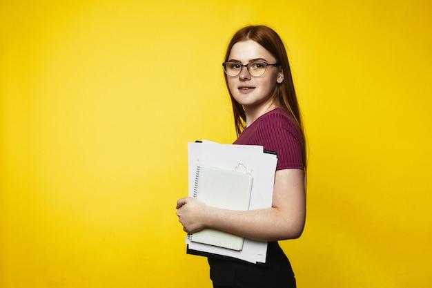Sorriu garota caucasiana ruiva está segurando cadernos e arquivos nas mãos Foto gratuita