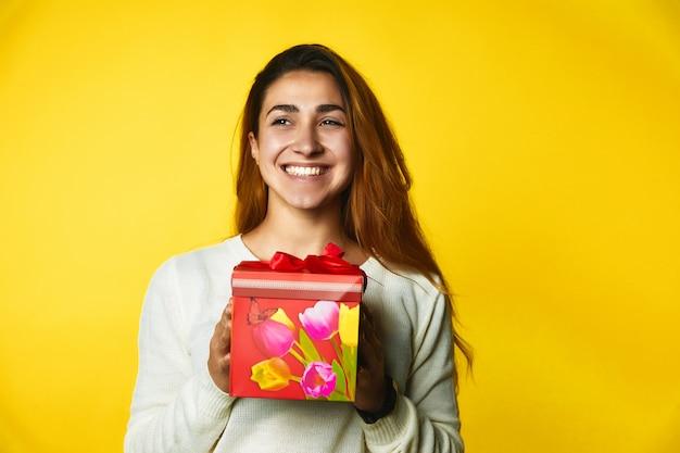 Sorriu garota caucasiana ruiva está segurando vermelho presente nas mãos, com rosto animado Foto gratuita