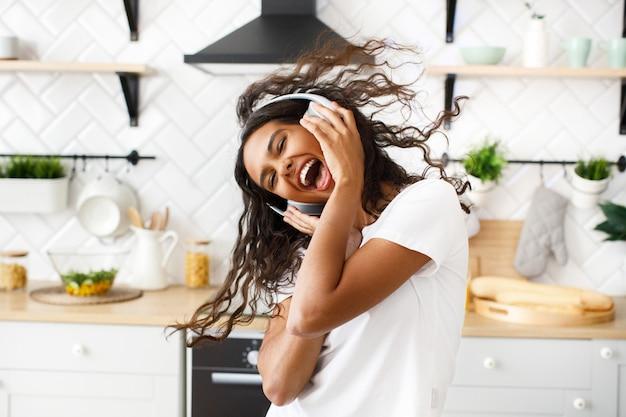 Sorriu hilariante mulata com cabelo desarrumado em grandes fones de ouvido sem fio, dançando alegremente com a boca aberta na cozinha moderna Foto gratuita