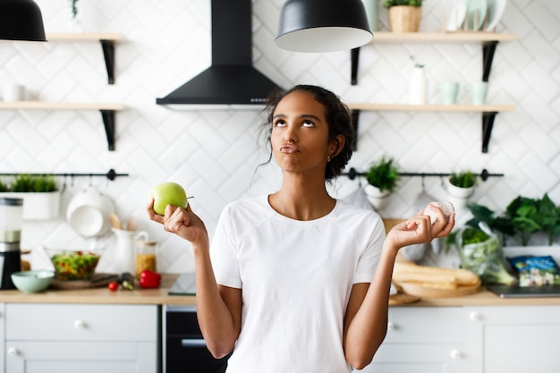 Sorriu mulata atraente está pensando em uma maçã com rosto hilariante e olhando para o topo na cozinha moderna branca Foto gratuita