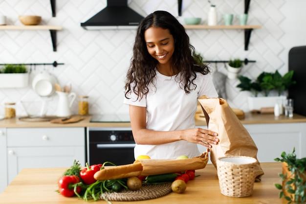 Sorriu mulata bonita está colocando pacotes com comida sobre a mesa na cozinha moderna Foto gratuita