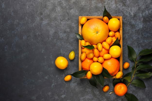 Sortidas frutas cítricas na cesta de armazenamento de alimentos, limões, laranjas, tangerinas, kumquats, toranja, vista superior Foto gratuita