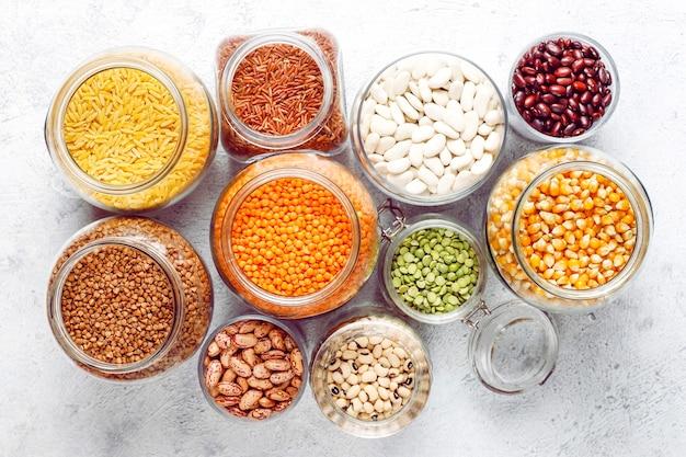 Sortido de leguminosas e feijões em diferentes tigelas em pedra clara. vista do topo. alimentos saudáveis de proteína vegana. Foto gratuita