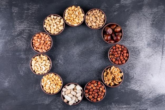 Sortido de nozes e frutas secas em um ciclo em forma de mini tigelas diferentes com nozes, pistache, amêndoa, amendoim, leigos Foto gratuita