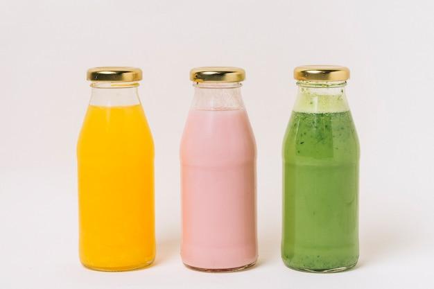 Sortido deliciosos smoothies de frutas em garrafas Foto gratuita