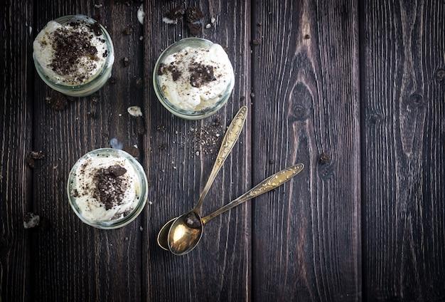 Sorvete com biscoitos de chocolate em potes de vidro. estilo rústico. Foto Premium