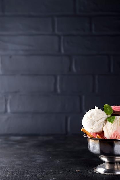 Sorvete de baunilha e rosa em uma tigela com bagas congeladas e cone de waffle Foto Premium