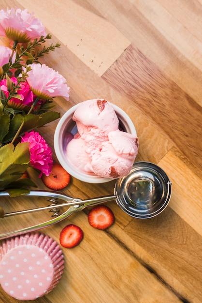 Sorvete-de-rosa na tigela perto de colher com fatias de frutas frescas e flores Foto gratuita