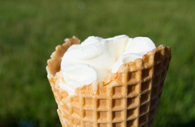 Sorvete no cone de waffle na grama turva Foto Premium