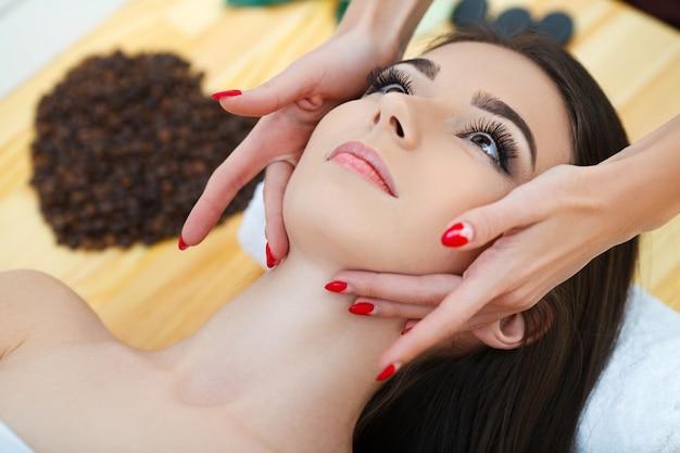 Spa. a mulher bonita nova que encontra-se na cama com corpo feliz dos termas e esfrega a pele no salão de beleza dos termas. conceito de relaxamento spa de aroma de saúde, tratamento e massagem corporal Foto Premium