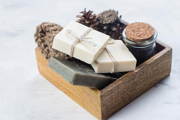 Spa, conceito de corpo de skincare de beleza. sabonete artesanal, esfoliação corporal de café e pincel para o corpo em madeira Foto Premium