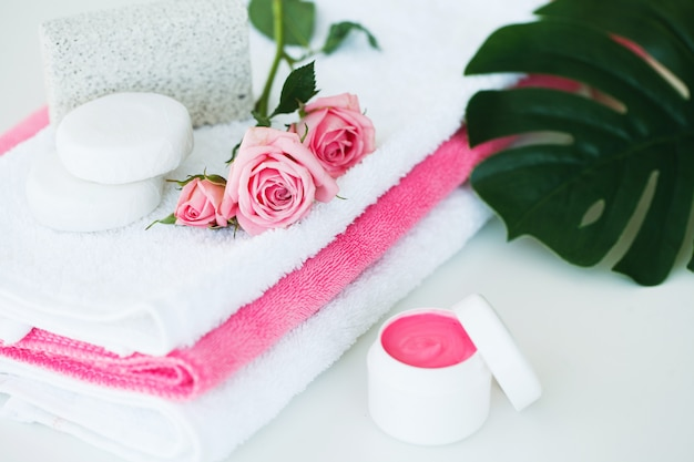 Spa, creme cosmaetic com pétalas de rosa e rosa flor na mesa branca Foto Premium