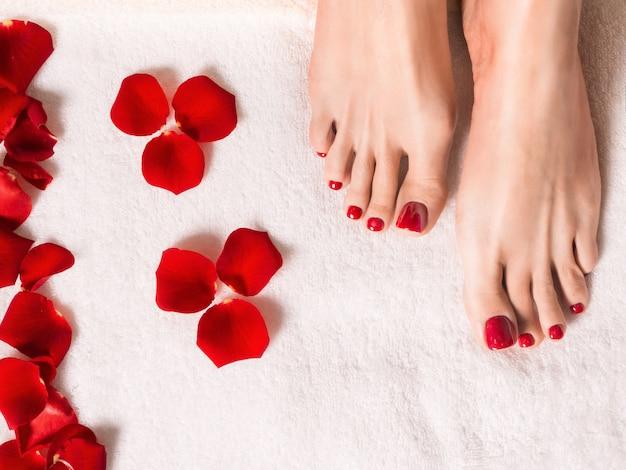 Spa e bem-estar. pés femininos com pétalas de rosa na toalha de terry. Foto Premium