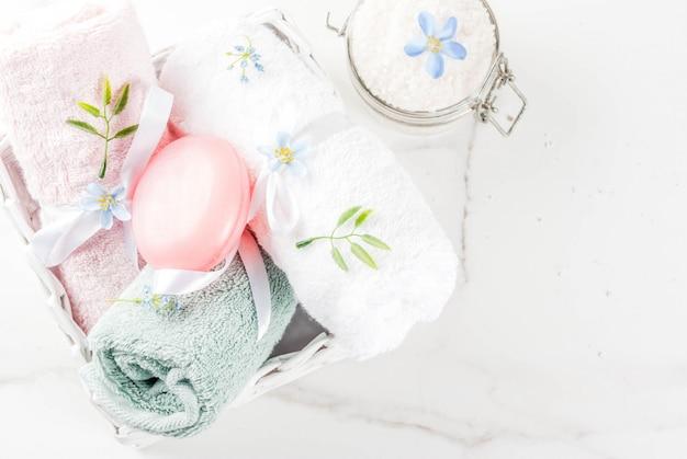 Spa relaxar e conceito de banho, sal marinho, sabão, com cosméticos e toalhas no banheiro Foto Premium