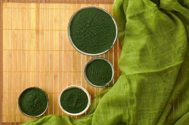 Spirulina algas, spirulina em pó em copos de cerâmica em esteira de bambu Foto Premium